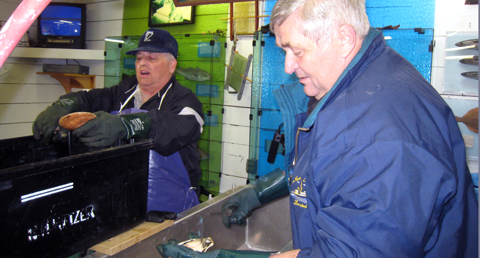 Norman Keizer (foreground) and Wallace Skinner, scallop shucking champions at the Fisheries Museum of the Atlantic, Lunenburg
