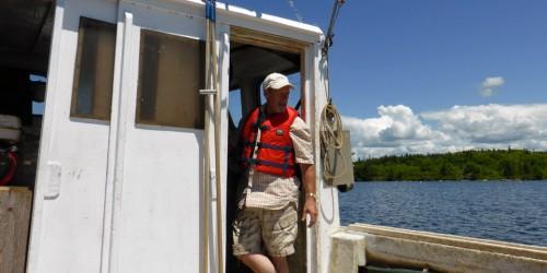 """The Oysterman"", Nolan D'Eon, on his boat at Eel Lake Oyster Farm, Ste. Anne du Ruisseau, Nova Scotia"