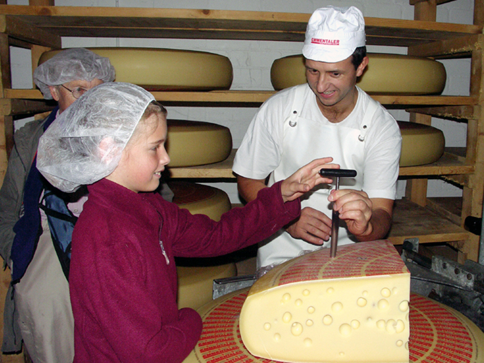 cheese master, Alfred Bieri-Meyes, shows a young visitor how to test the Emmantaler cheese for quality, Blumenstein, Switzerland