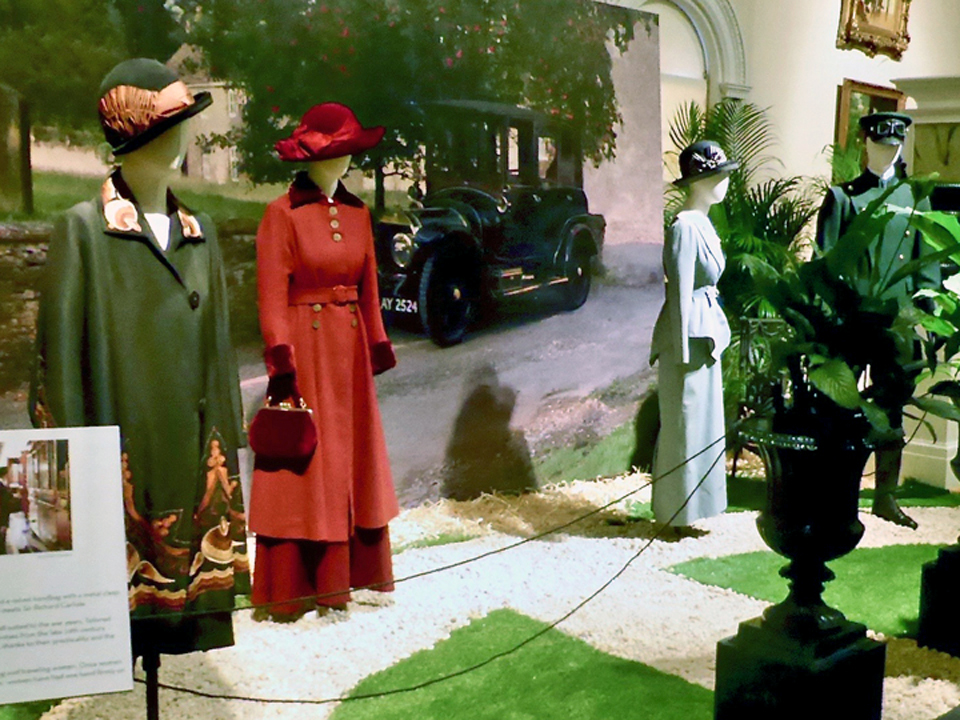 Lady Edith's Arts and Crafts style coat, Lady Mary's red wool coat with velvet trim, Lady Sybil's tailored suit, and the chauffeur costume, Lightner Museum, St. Augustine, FL